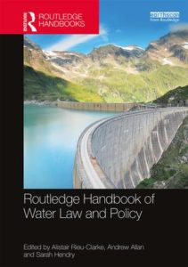 book cover for the 'Routledge Handbook of Water Law and Policy' showing a dam in the mountains